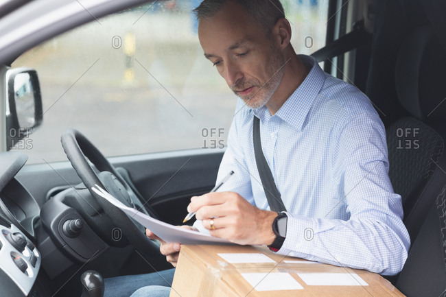 Side view of delivery man writing on paper in delivery van