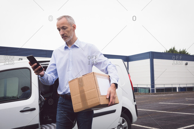 Delivery man using mobile at warehouse on a sunny day