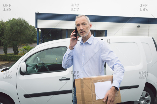 Delivery man talking on mobile phone at warehouse on a sunny day