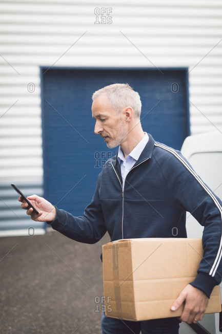 Close-up of delivery man using mobile phone at warehouse