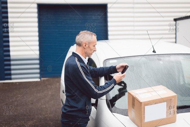 Delivery man using mobile phone at warehouse