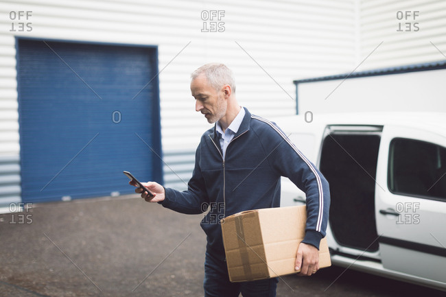 Delivery man using mobile phone at warehouse on a sunny day