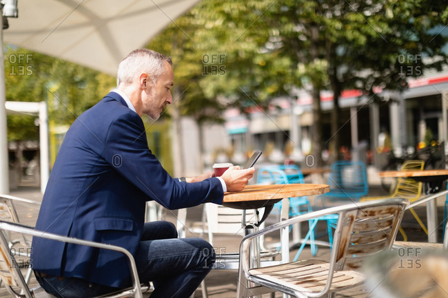 Side view of businessman using mobile phone at outdoor cafe