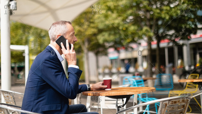 Side view of businessman talking on mobile phone at outdoor cafe