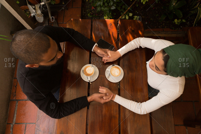 Overhead of couple holding hand in cafe