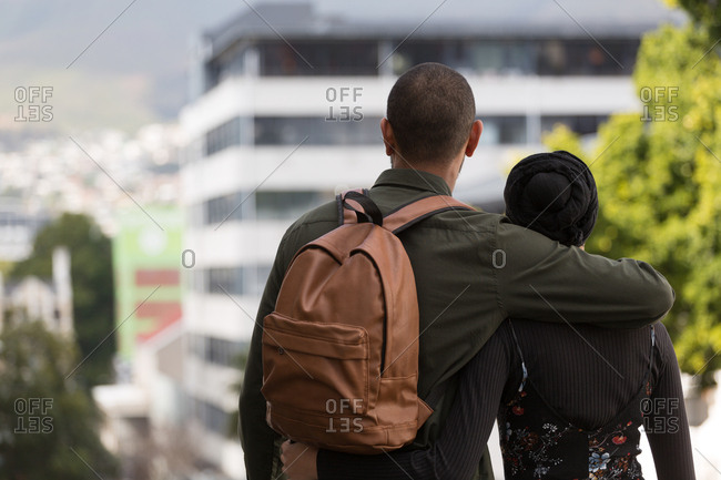 Rear view of couple standing with arm around in city