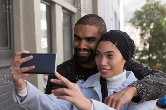 Happy couple taking selfie on city street