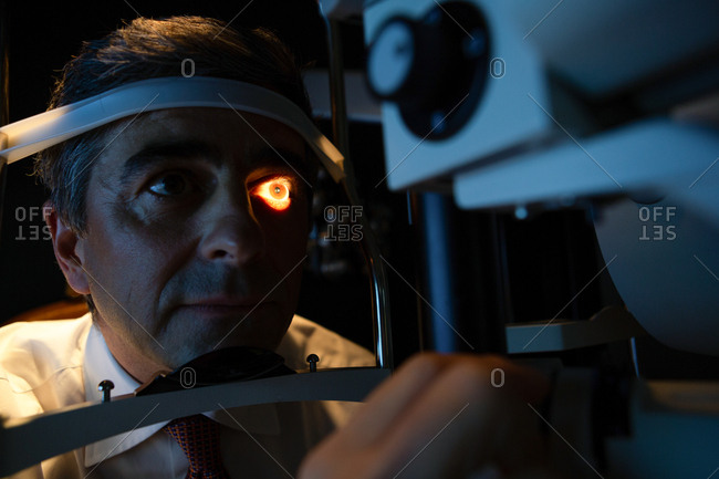 Optometrist examining patient eyes with slit lamp in clinic