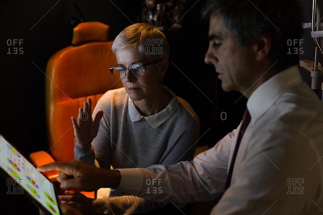 Optometrist explaining eyesight report over digital tablet in clinic