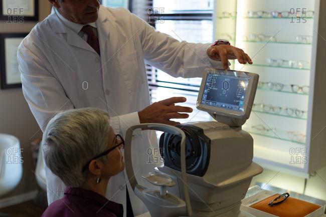 Optometrist explaining eyesight report on autorefractors screen in clinic
