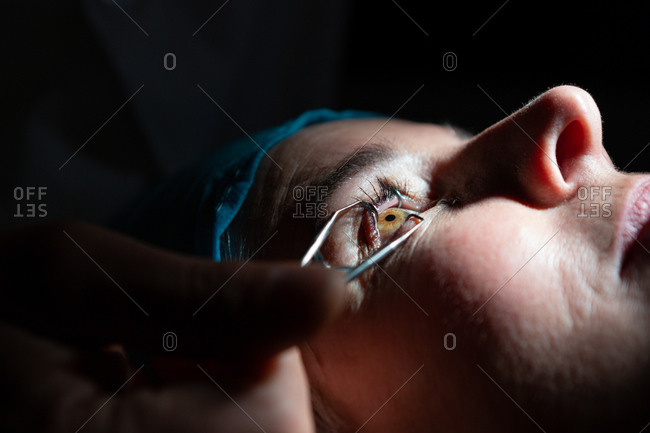 Close-up of optometrist examining patient eyes with eye test equipment in clinic