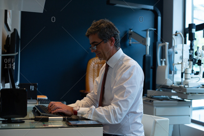 Side view of optometrist using desktop pc in clinic
