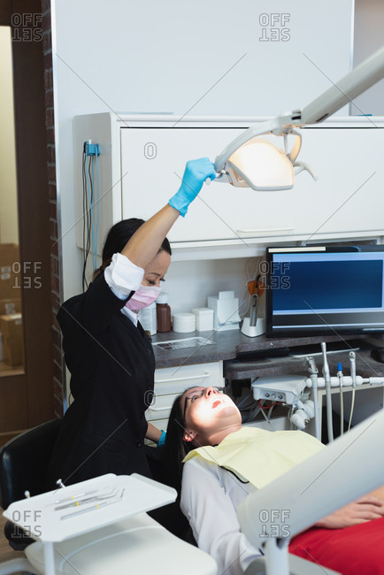 Female dentist examining a patient in dental clinic