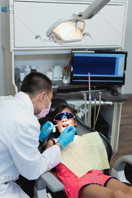 Male dentist examining a patient with tools in clinic