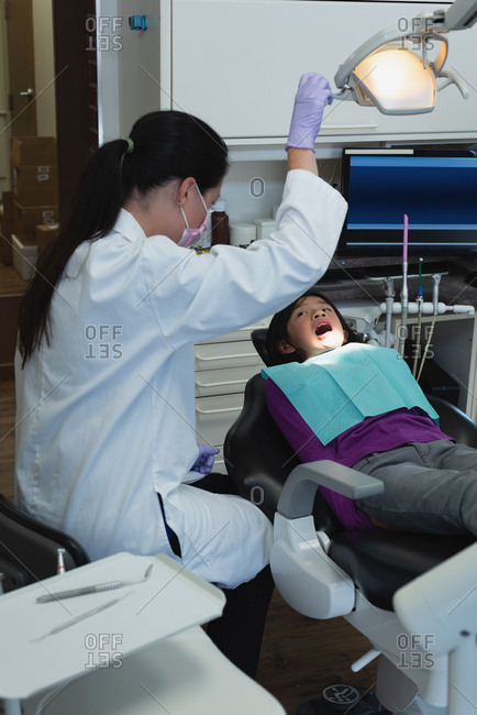 Female dentist and nurse examining patient in clinic