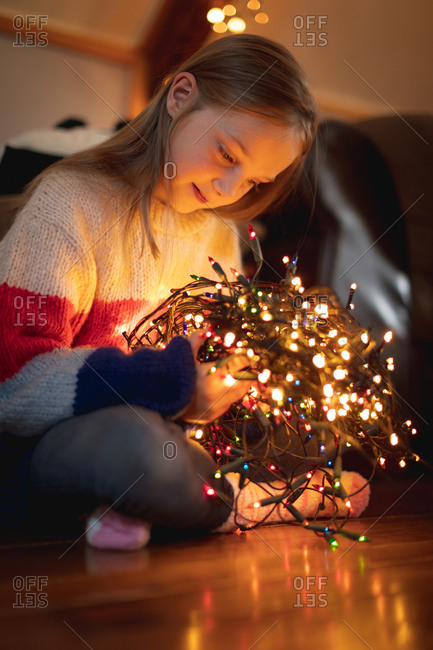 Close-up of girl looking at illuminated fairy lights at home
