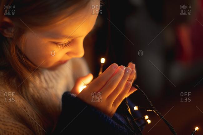 Close-up of girl looking at illuminated fairy lights at home