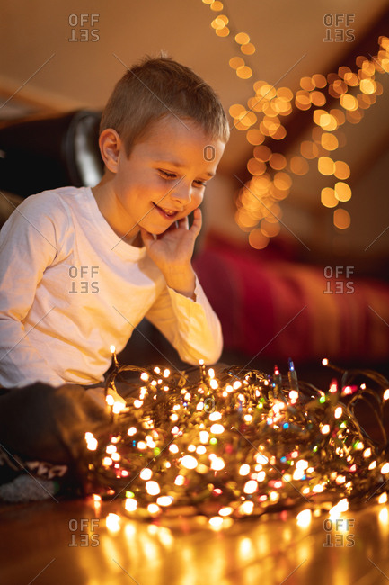 Smiling boy looking at illuminated fairy lights at home
