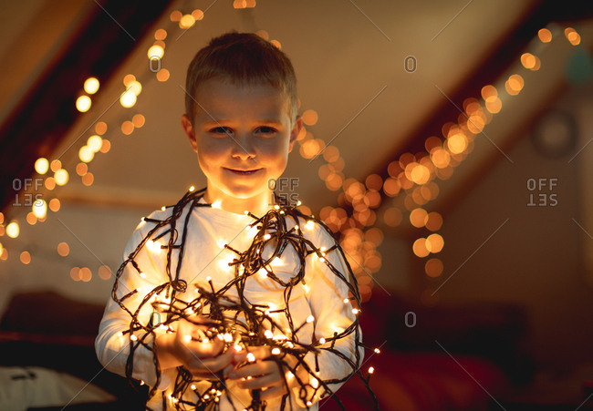Smiling boy holding illuminated fairy lights at home
