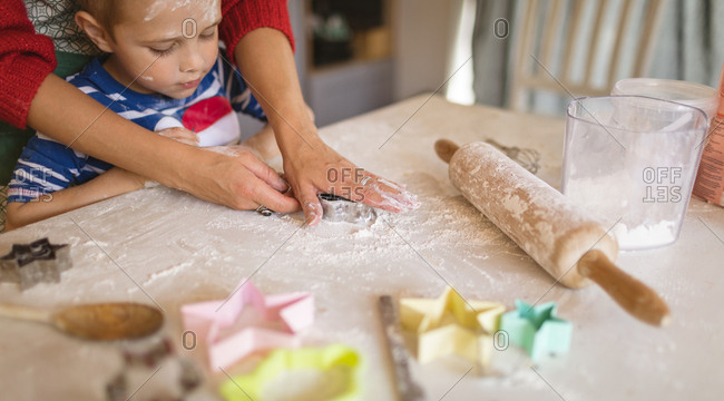 Son looking at mother cutting the cookies in the kitchen