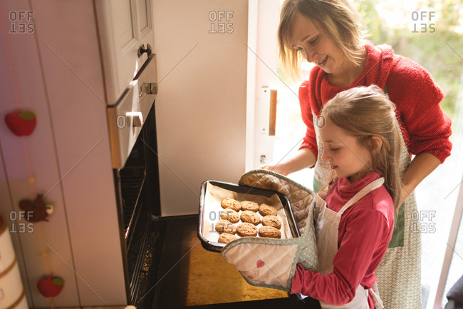 Mother and daughter looking at the baked cookies in the kitchen
