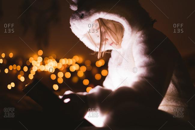 Girl in hooded jacket using digital tablet against Christmas lights