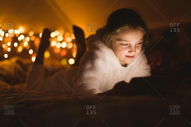 Smiling girl using digital tablet against Christmas lights