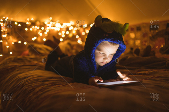Concentrated boy in blue jacket using digital tablet against Christmas lights