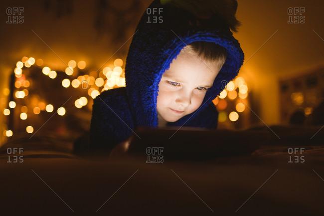 Close-up of boy in blue jacket using digital tablet against Christmas lights