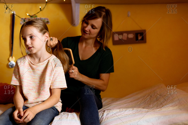 Mother combing daughters hair on bed at home