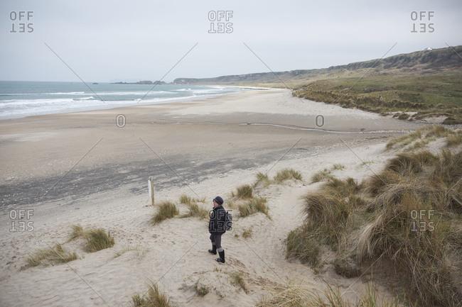 April 11, 2018: Woman walking along sand swept beach exploring White park bay, Northern Ireland, United Kingdom