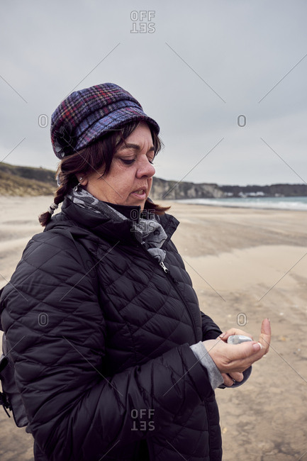 April 11, 2018: Woman walking along sand swept beach picking rocks, Northern Ireland, United Kingdom