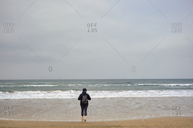 Woman walking into the north atlantic ocean , Northern Ireland, United Kingdom, 2018