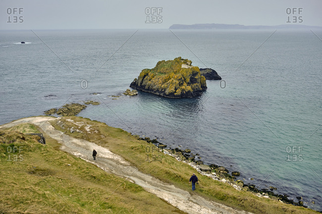 Hikers walking along rough coast of the north atlantic ocean, Ballycastle, Northern Ireland, United Kingdom, 2018