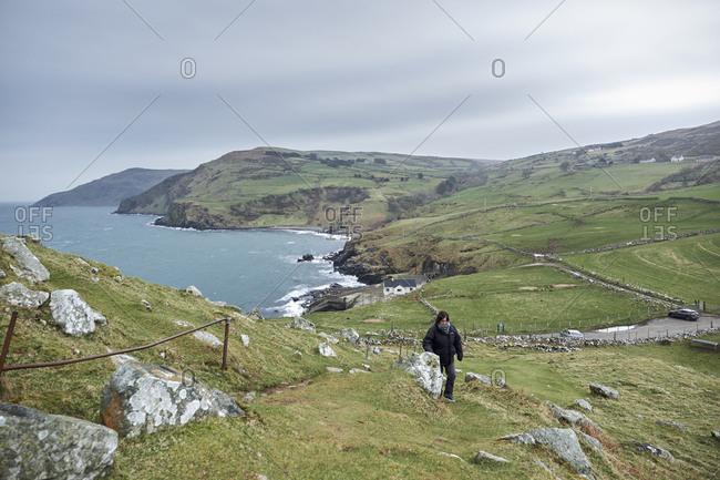 April 12, 2018: Tourist climbing Torr's head, County Antrim Northern Ireland, United Kingdom