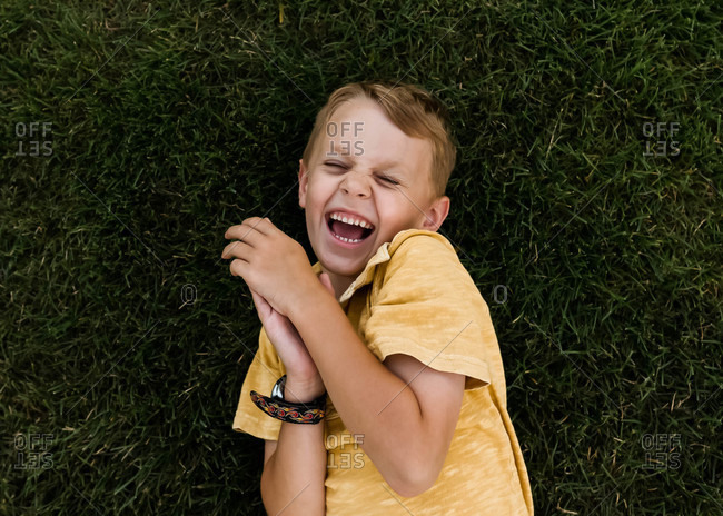 Overhead portrait of young boy laughing in the grass