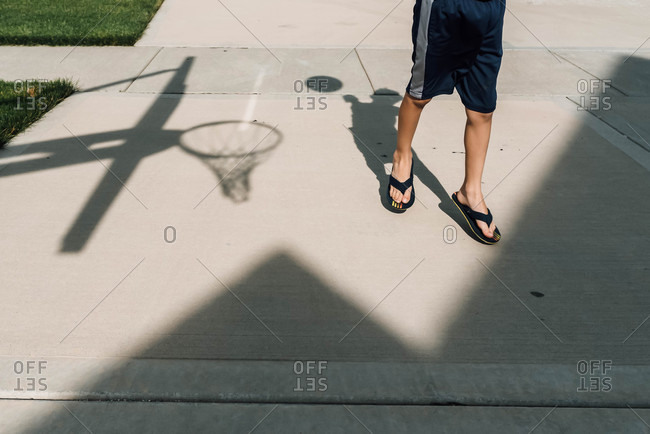 Shadow of a young boy shooting a basketball in a home driveway