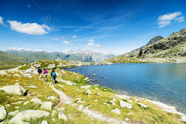 Hikers on footpath on the shore of lake Bergsee, Spluga Pass, canton of Graubunden, Switzerland, Europe