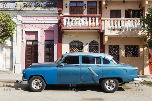 November 20, 2016: Old blue American car parked in front of old buildings, Cienfuegos, UNESCO World Heritage Site, Cuba, West Indies, Caribbean, Central America