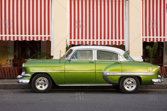 November 20, 2016: Green vintage American car parked in front of cafe, Cienfuegos, UNESCO World Heritage Site, Cuba, West Indies, Caribbean, Central America