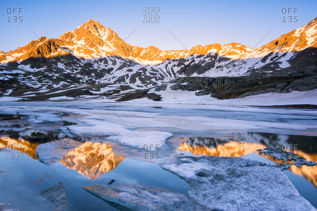 Tre Signori peak reflected in an alpine lake at thaw, Gavia Pass, Val Camonica, Stelvio National Park, Brescia Province, Lombardy, Italy, Europe