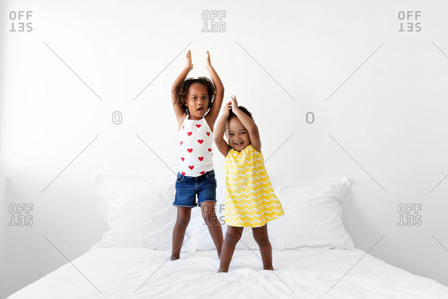 Two girls standing together on bed with their arms raised
