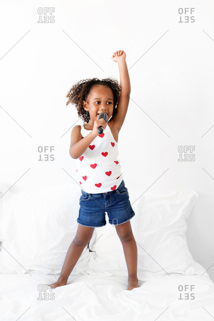 Girl standing on the bed with arm raised singing into a hairbrush