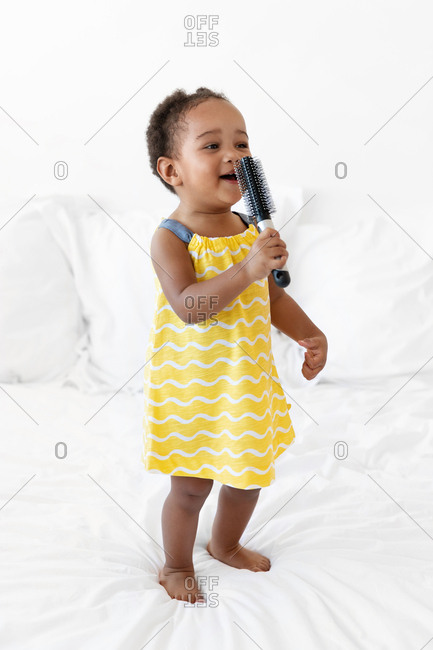 Little girl standing on the bed singing into a hairbrush