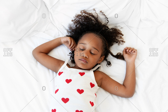 Portrait of a sleeping girl with curly hair lying down on bed