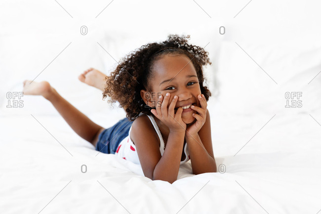 Smiling girl resting on bed with head in hands
