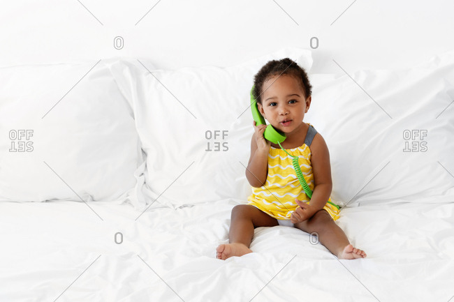 Toddler child sitting on bed and pretending to talk on the phone