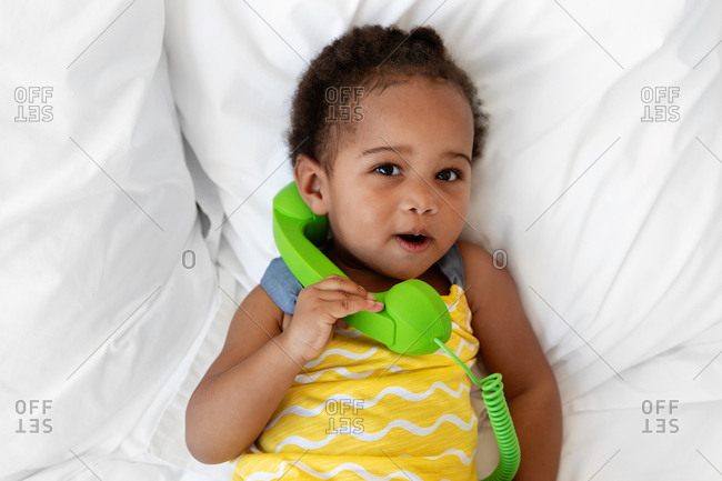 Portrait of a toddler child pretending to talk on the phone