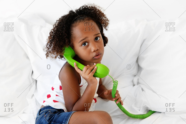 Girl sitting on bed pretending to talk on the phone