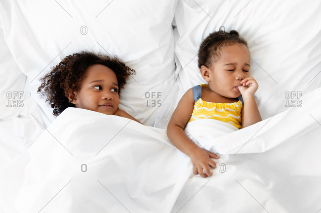 Girl in bed looking at younger sister who is asleep and sucking her thumb